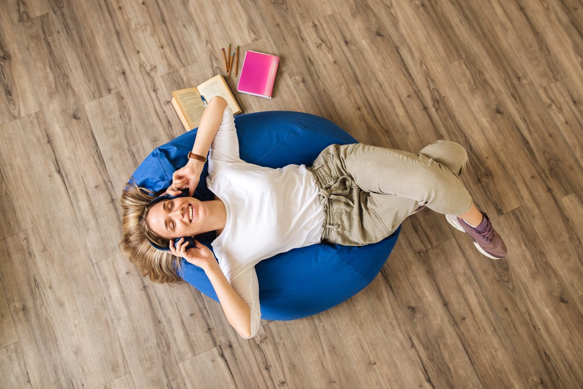 A woman listens to something on her headphone while laying on a bean bag chair.