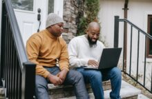 A father and teenage son sit out on a porch with a laptop discussing how to add rent and utilities to your credit report.