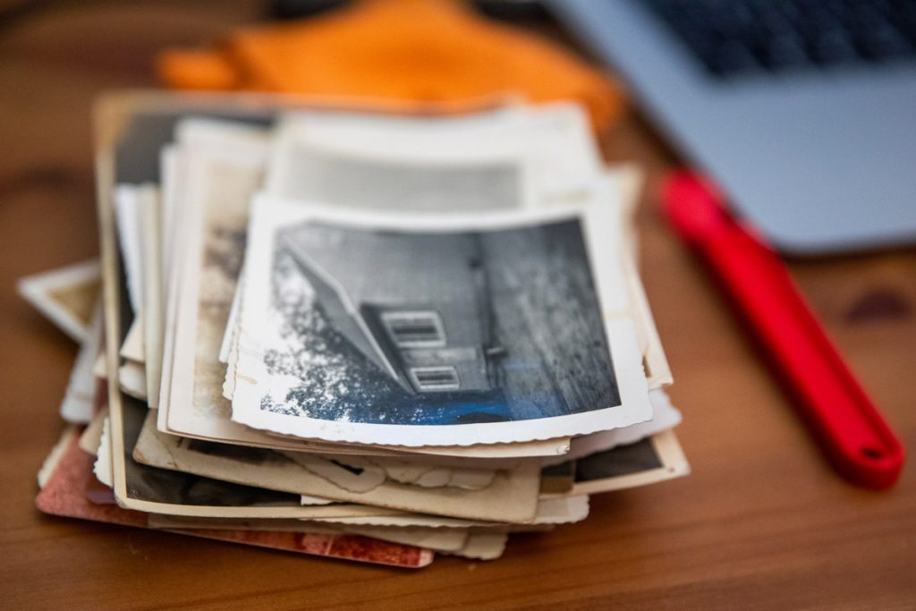 A stack of old black and white photographs sits on a person's desk.